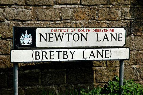 Newton Lane changes to Bretby Lane half way along its length, hence the two names on the street sign