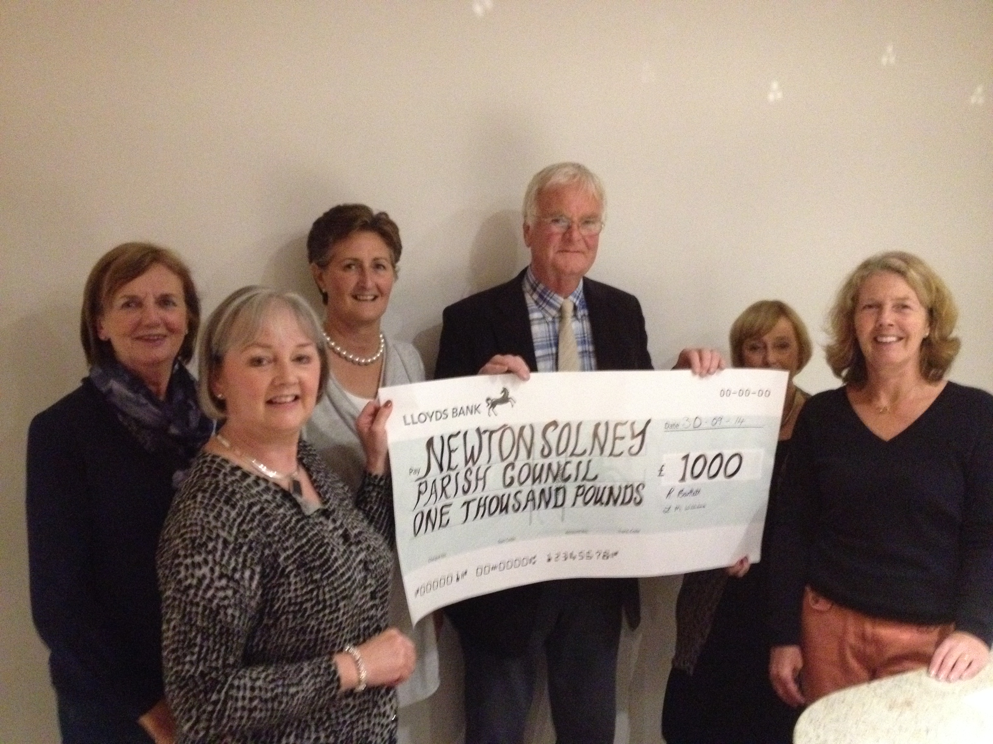 Members of the WI present a cheque to Fred Hill, chairman of Newton Solney Parish Council for £1,000.